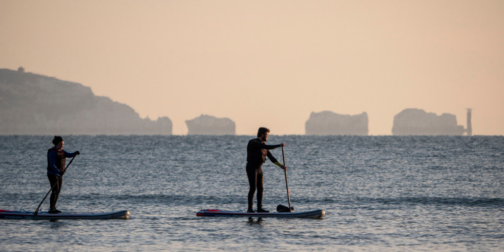 Visit Milford on Sea paddleboarding by The Needles